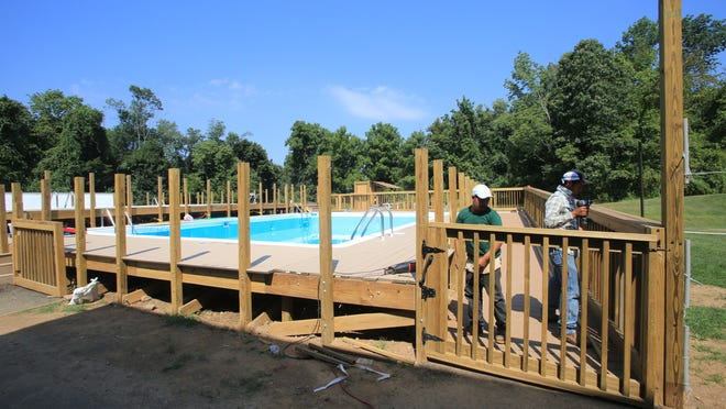 Workers dismantle the fence surrounding a portable swimming pool at Chestnut Ridge Middle School on Wednesday.