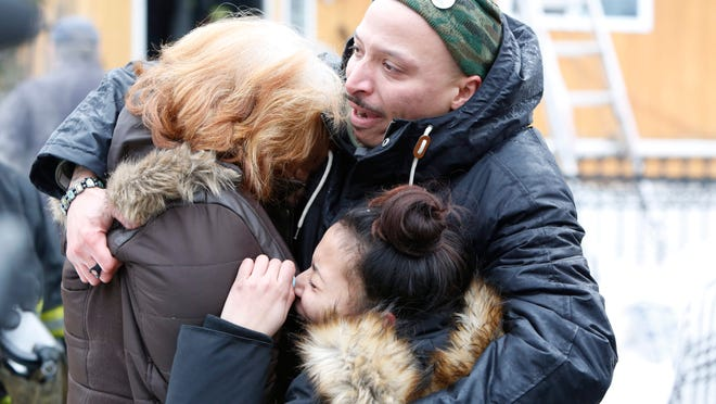 Residents cry after hearing that a dog didn't survive a house fire Monday at 13 S. 12th Ave. in Mount Vernon. Officials said the blaze was sparked by a candle that tipped over.