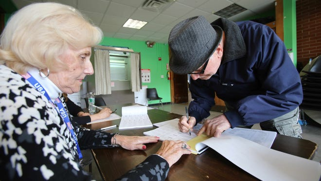 Carlo Masci, right, signs in with poll worker Patricia Barr, left, before voting in the Village Elections at Carver Center in Port Chester on March 18, 2015.