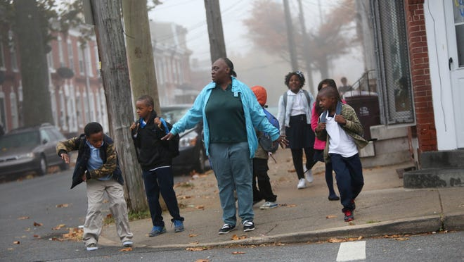 Denise West, 53, walks her two grandsons along with several neighborhood children down the 900 block of North Pine Street to nearby Stubbs Elementary School.