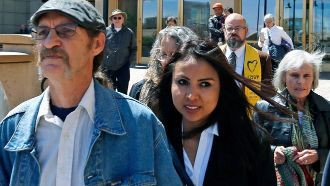 FILE - In this May 3, 2017 file photo, sanctuary church resident Ingrid Encalada Latorre, center, leaves the Jefferson County Courthouse, in Golden, Colo. Latorre, who sought sanctuary at a Quaker meeting house in Denver to avoid U.S. immigration authorities, has asked Colorado's governor for a pardon that might allow her to fight deportation. Latorre, a 33-year-old native of Peru, asked for a pardon Thursday, Aug. 31, 2017 after a suburban Denver judge rejected her appeal of a 2010 case in which she pleaded guilty to a felony charge of possessing falsified or stolen identification papers. (AP Photo/Brennan Linsley, File)