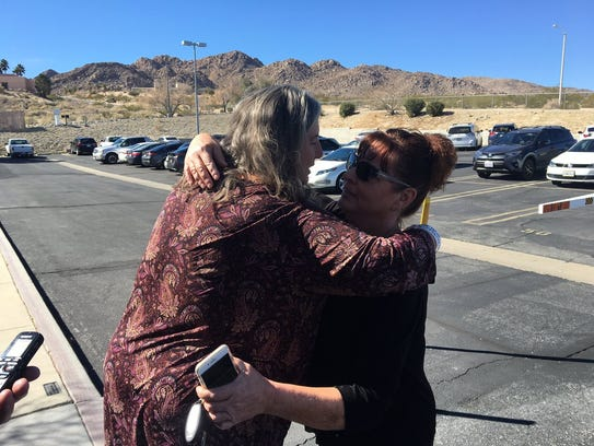 Mona Kirk, on the left, hugs a supporter after being