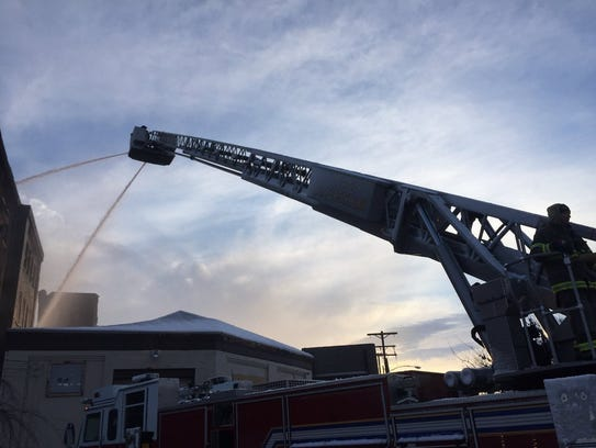 York firefighters use an aerial ladder to blast water