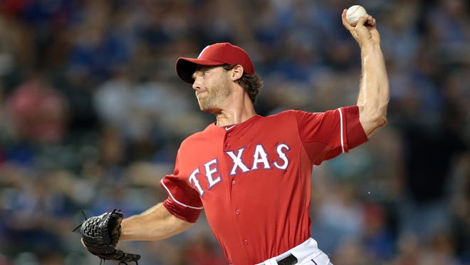 Texas Rangers reliever Neal Cotts pitches against the Kansas City Royals during a game at Globe Life Park in Arlington, Texas, in August 2014. Cotts has signed with the Milwaukee Brewers.