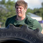 Fowlerville's Logan Miller competes in the Sandbag Carry as his teammates watch. Each bag weighs 55 pounds.