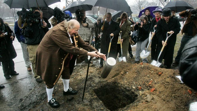 Ralph Archbold, left, portrays Benjamin Franklin as he tosses a time capsule into a hole beside the Benjamin Franklin Parkway in Philadelphia.
