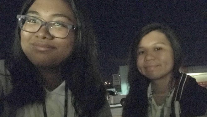 VIBEster Seanna Bataclan and JFK Student Camile Manalac wait for their school bus to arrive the morning of March 9.