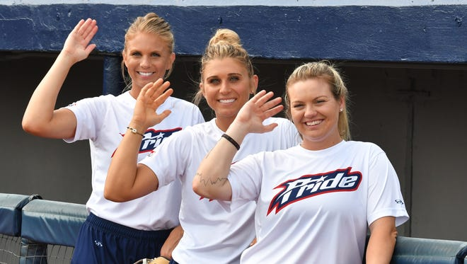 "Three former FSU players for the USSSA Pride do the ""Tomahawk Chop"" before a game in Viera: from left, pitcher Jessica Burroughs, first baseman Alex Powers and third baseman  Jessie Warren."