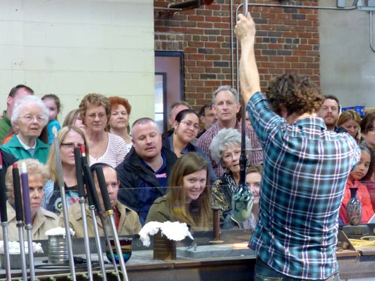 Dozens of spectators watch as a glassblower works during the Virginia Hot Glass Festival.
