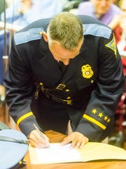 New Vineland police chief Rudolph Beu signs paperwork during his swearing in at Vineland City Hall on Tuesday, January 3.
