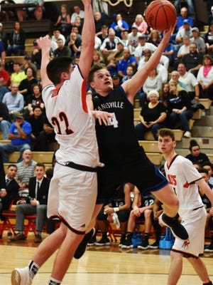 Clayton Foreman goes up for a layup against Meadowbrook's Davis Black during visiting Zanesville's 52-49 win on Tuesday night at The Corral. The win clinched the East Central Ohio League title.