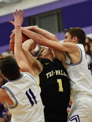 Senior Cam Mercer is tied up going through the lane during the first half of Tri-Valley's 74-38 loss to Logan in a Division I central district game at Jim Myers Gymnasium. The Scotties were outscored 43-12 in the second half.