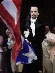 Lin-Manuel Miranda proudly waves a Puerto Rican flag