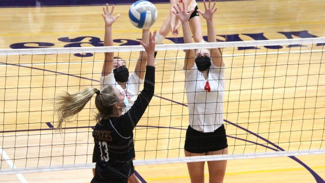 The Coldwater duo of Laynee Paarlberg (left) and Abby Herman (4) look for a block while teammate Violet Waltke (9) looks on in early season action.