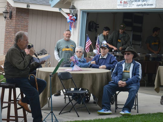 Jerry Barkley, left, speaks at the Paint It Forward for Heroes event on Saturday.