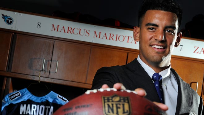 Titans first-round draft pick Marcus Mariota, in a shirt borrowed from coach Ken Whisenhunt, poses at his locker at Saint Thomas Sports Park on Friday.