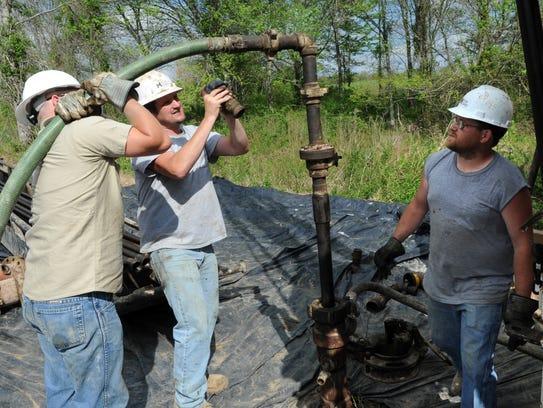 Miller Energy Resources rig hand Jake Sumner, left,