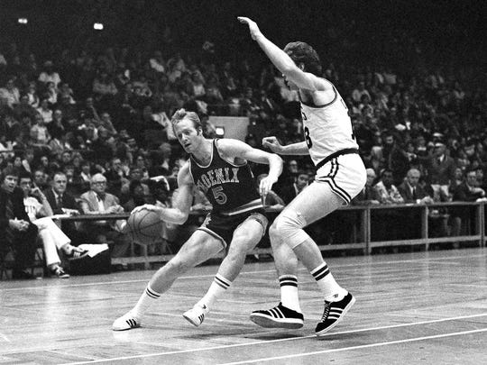 Phoenix Suns' Dick Van Arsdale (5) dribbles the ball as he drives around Boston Celtics' Dave Cowens, in  1973.