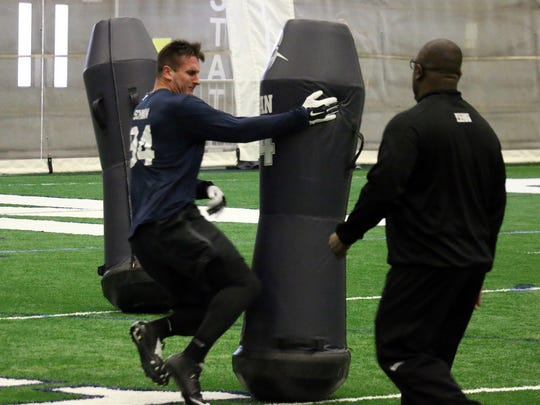 Harrisburg defensive end Evan Schwan runs a Pro Day drill under the watch of line coach Sean Spencer. Schwan said he's confident of making an NFL team as a special teams' performer.