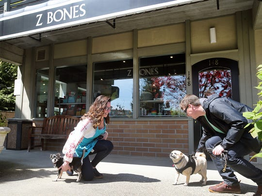 Katia Buskirk, left, owner of the new Z Bones Pet Mercantile at the Winslow Green, on Bainbridge Island is with her dog Zachary as she greets Jeremy Ghent and his dog Che. The store is named after Zachary, a rescue dog.