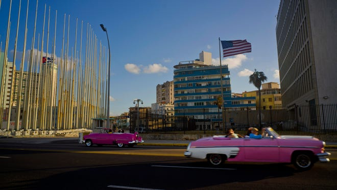 Tourists ride in classic American convertible cars past the U.S. Embassy (right) in Havana on Jan. 12, 2017.