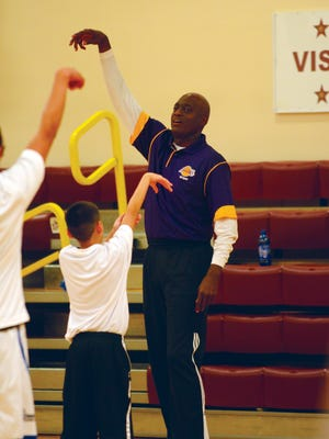 Former Los Angeles Laker Michael Cooper shows campers how to follow through on a basketball shot at his clinic Friday at Rocky Boy High School.
