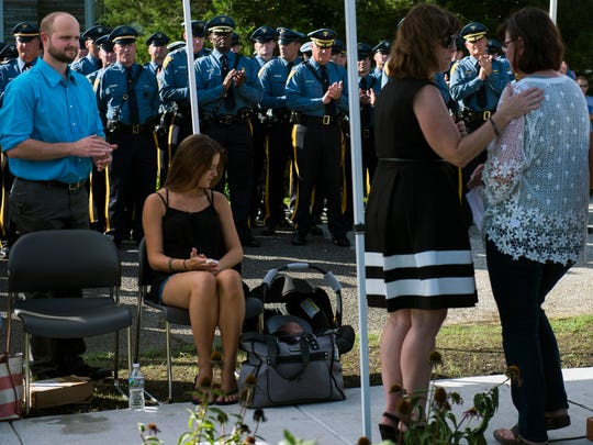 Jordan McCarson, left, looks over at her son Eli McCarson at a dedication ceremony for her late husband at Trooper Eli McCarson Memorial Park Thursday in Mantua.