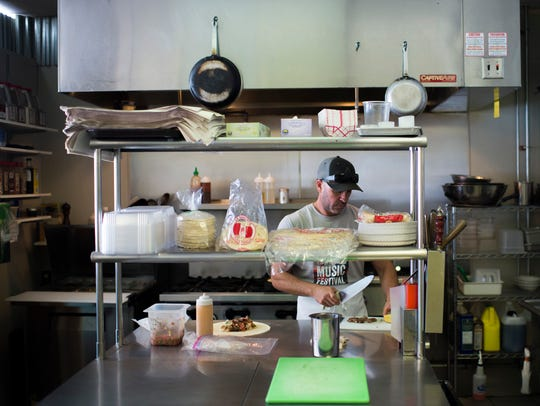 Owner Joe Gentile prepares a burrito in the kitchen of Local Links Market Cafe in Haddon Heights. The cafe hosts a Fish Taco Happy Hour on Fridays.