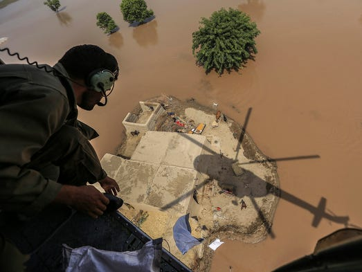 A Pakistani soldier throws food bags to people stranded in a flooded area on Sept. 15 in Shujabad.