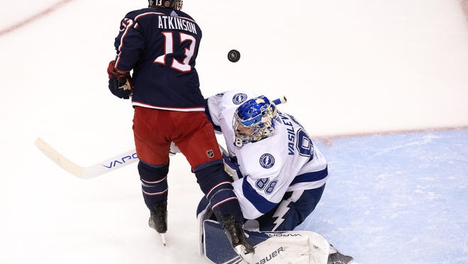 Columbus Blue Jackets right wing Cam Atkinson (13) bumps the puck free from Tampa Bay Lightning goaltender Andrei Vasilevskiy (88) on his way to scoring during the second period in Game 4 of an NHL hockey first-round playoff series in Toronto on Monday, Aug. 17, 2020.
