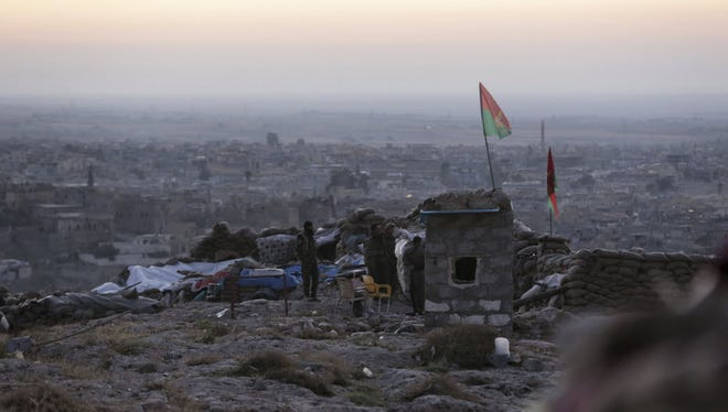 Kurdish fighters are on watch in the early morning as they fight against the Islamic State group in Sinjar, Iraq, on Nov. 13.