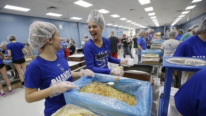 """Chandler High girls volleyball players Mikaila Williams and Lauren Weintraub (right) packs meals at """"Feed My Starving Children"""" on Thursday, Oct. 13, 2016."""