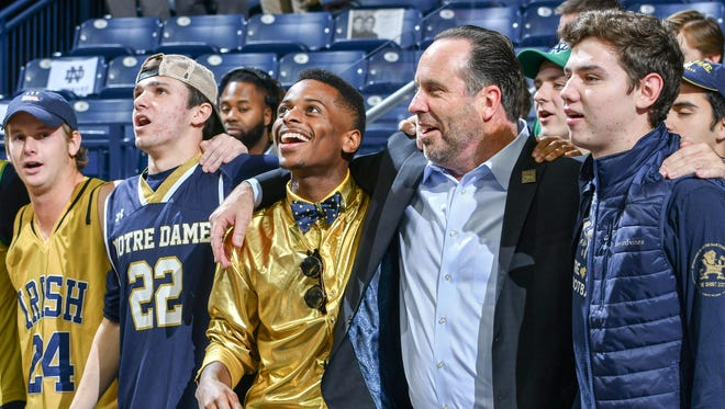 Notre Dame Fighting Irish head coach Mike Brey celebrates in the student section after Notre Dame defeated the Mount Saint Mary's Mountaineers.