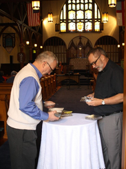 Bill Strauss, left, and pastor Rick Kautz arrange CDs