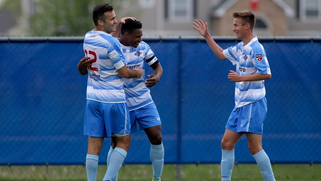 Lansing United's DeJuan Jones, center, is congratulated by John Freitag, left, who assisted Jones, and Danny Wright, right, after scoring the first goal against the Michigan Bucks, Saturday, May 12, 2018, in East Lansing, Mich. The teams played to a 2-2 draw.