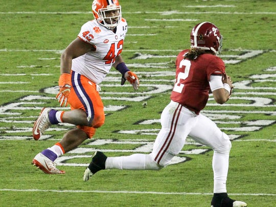 Clemson defensive tackle Christian Wilkins (42), left, chases Alabama quarterback Jalen Hurts (2) during the second quarter of the National Championship game on Monday at Raymond James Stadium in Tampa, Florida.