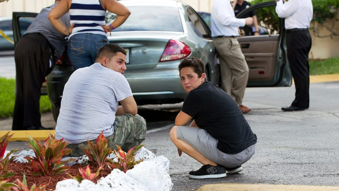 Two people sit behind a police car as Miami police officers investigate a murder on Thursday, in Miami.