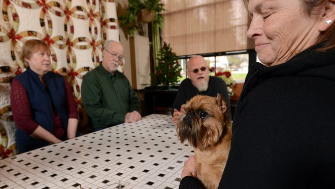 Newton, a Brussels Griffon, is held by his handler Susan DePew of Akin, S.C., while some of his co-owners (left to right) Janet and Mike Bazell, form Logan, and Jeff Bazell, from Bremen, talk about Newton's recent win at the National Dog Show in Philadelphia.
