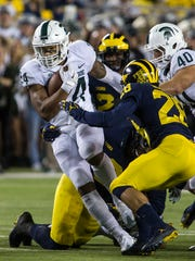 Michigan State running back Gerald Holmes (24) rushes through tackles and into Michigan defensive back Brandon Watson (28) in the first quarter of an NCAA college football game in Ann Arbor, Mich., Saturday, Oct. 7, 2017. (AP Photo/Tony Ding)