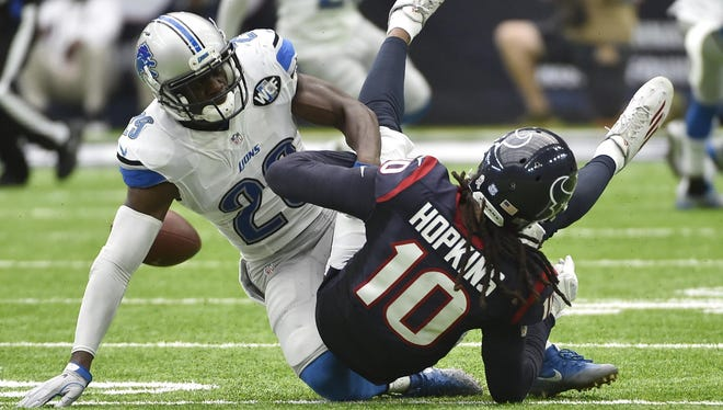 Lion Johnson Bademosi knocks the ball loose from Houston's DeAndre Hopkins in the third quarter. The Lions recovered the ball, but officials ruled in an incomplete pass.