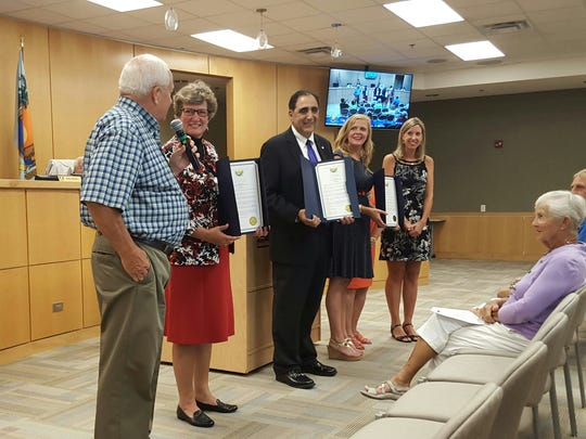 City Council Chairman Bob Brown (left) presents school administrators from Tommie Barfield Elementary, Marco Island Charter Middle School and Marco Island Academy with proclamations recognizing their schools' outstanding achievements.