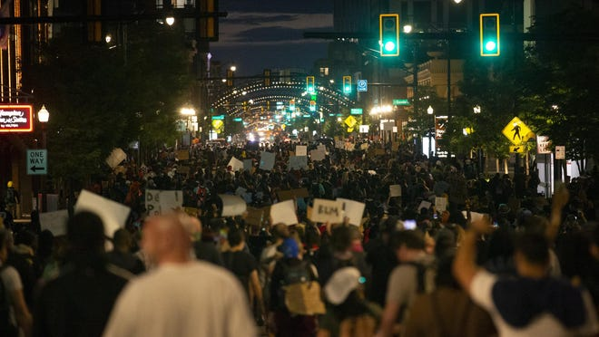 A large group of demonstrators in cars and on foot march north on High Street through the Short North during a peaceful protest for George Floyd on Monday, June 1, 2020. The group made it from the Ohio Statehouse all the way to Lane Avenue near Ohio State's campus.
