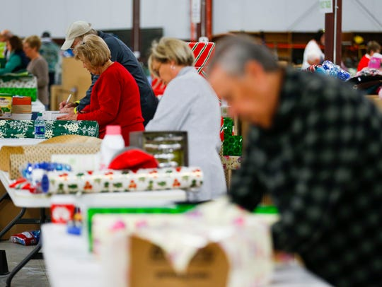 About 50 volunteers, wrap presents for the 213 families
