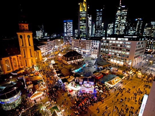 People gather on a small Christmas market in central Frankfurt, Germany, Wednesday, Dec. 19, 2018.