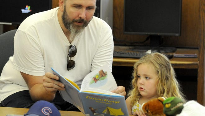 Rodney Carlson of Green Bay reads a book to his daughter, Anabelle, during the 2012 Summer Reading Program at the Brown County Central Library in Green Bay.