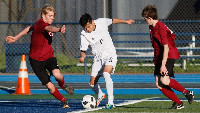 Pleasant Valley High's Daniel Rodriguez, center, dribbles by West Valley's Gideon Ferrier, left, in the Vikings' 6-1 win in a Northern Section Division I semifinal match Thursday in Chico.