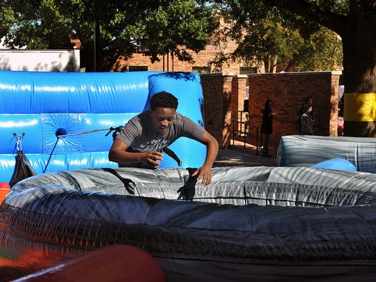 Preston Busby, a Midwestern State University criminal justice major, plays the human-sized version of the Hungry Hungry Hippo game during the MSU Homecoming Picnic Wednesday in Sunwatcher Plaza.