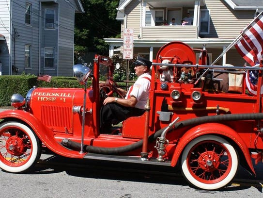Al Fisher drives an antique fire apparatus in the 2016