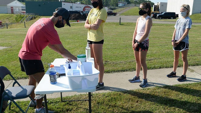 Fairview High School cross country runners line up to have their temperatures taken by coach Dino Montagna, left, before practice Thursday, July 2, 2020 at Fairview High School. The safety protocols are taken because of the COVID-19 pandemic.