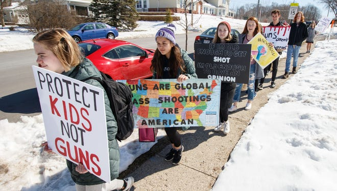 A group of students march from Oconomowoc High School to the city green during a student walkout/rally to raise awareness about gun violence and school safety on Friday, April 20, 2018. The date coincides with the 19th anniversary of the Columbine shooting tragedy.